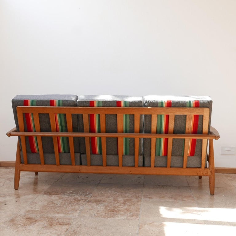 A smart three-seat sofa by design legend Hans J. Wegner.   Denmark, circa 1955-1965.  Solid oak, original upholstery which is perfectly usable but has some signs of age, can be updated in house at cost.  Good condition and timeless
