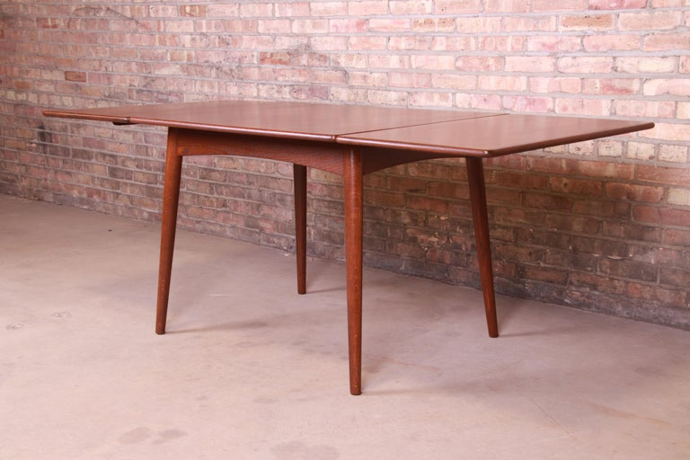 A rare and exceptional Danish Modern drop-leaf dining table  By Hans J. Wegner for Andreas Tuck  Denmark, 1950s  Teakwood top, on tapered dowel oakwood legs with arched aprons.  Measures: 39