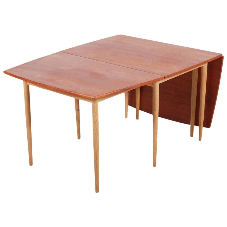 Very nice drop-leaf dining table designed by the Danish designer Hans Wegner and manufactured by Andreas Tuck. Made in Denmark, 1960.  The table is made of a combination of two wood species, Oak for the feet and veneered Teak for the top. Up to