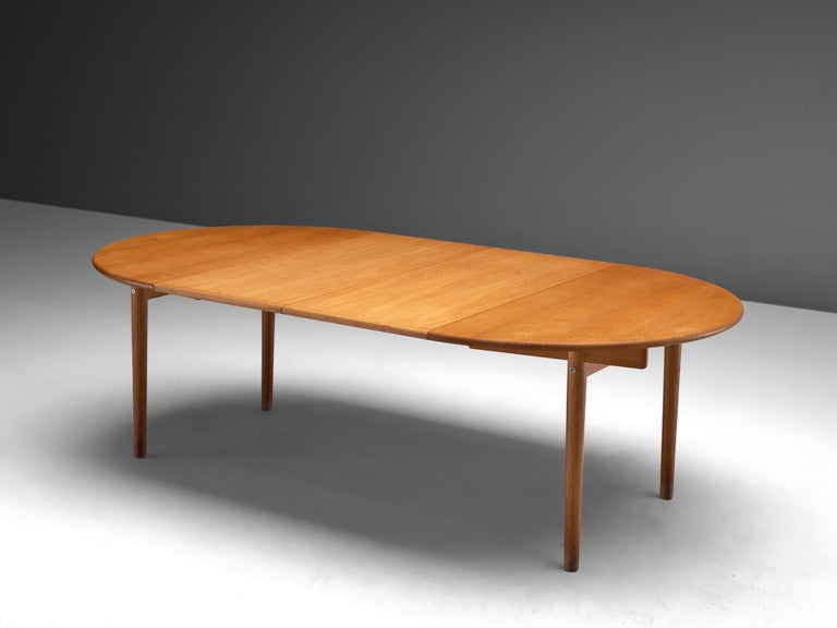 Hans J. Wegner for PP Mobler, PP70 dining table', oak, Denmark, 1975.  This extendable dining table designed by Hans J. Wegner is executed in oak and has additional leaves in order to expand the piece 126 cm to 230 cm. The table features a modest