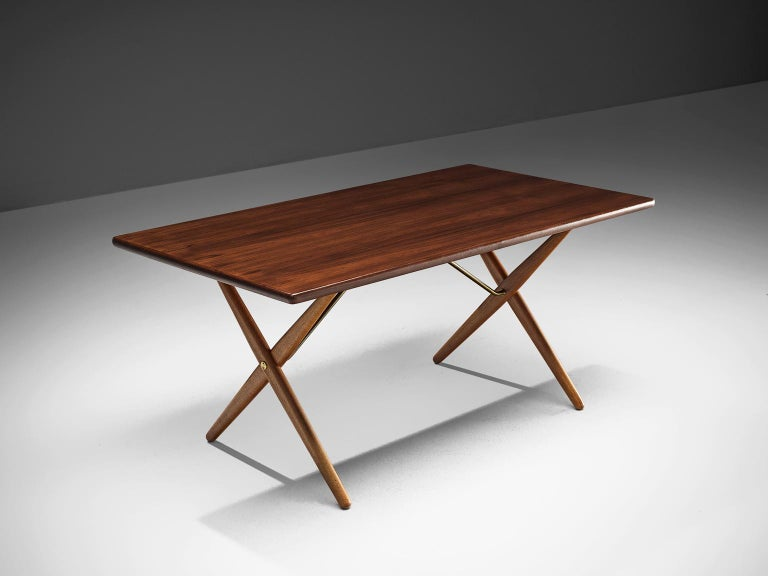 Hans J. Wegner for Andreas Tuck, table model AT-303, teak, oak and metal, Denmark, 1955.  Dining table with elegant X-shaped legs by Hans Wegner. This table is considered as one of the best known designs from Wenger. From a distance, this table,