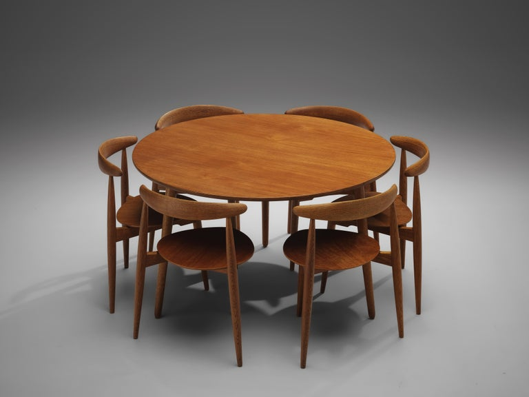 Hans J. Wegner for Fritz Hansen, set of 6 'Heart' chairs FH4103 and dining table, teak, oak, Denmark, 1953  This dining set, consisting of a round dining table and six dining chairs model FH4103, is designed by Hans Wegner in 1953. The chairs are