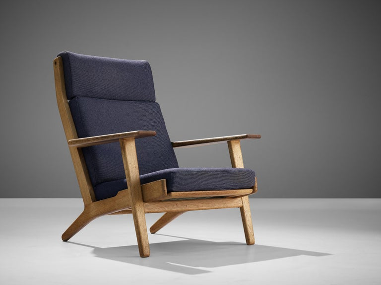Hans J. Wegner for GETAMA, lounge chair model 'GE290', oak, dark blue woolen upholstery, Denmark, design 1959.  Hans J. Wegner designed the GE290 with an inclined seating and backrest which created a comfortable lounge chair. Besides loose cushions