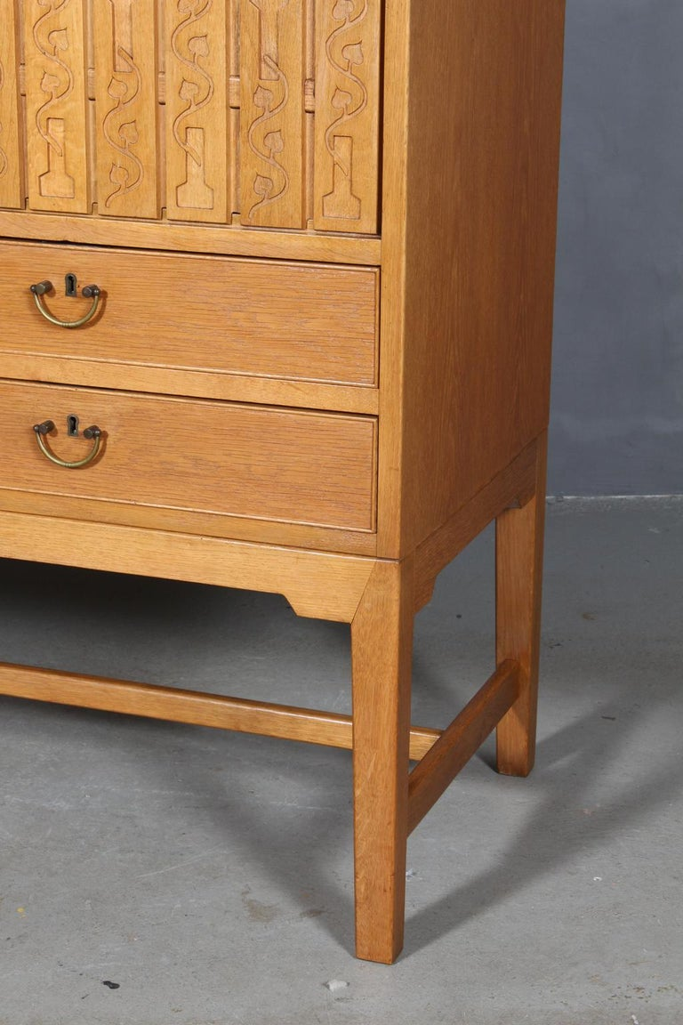 Hans J. Wegner cabinet in oak.  Four drawers with handle a lock in brass (keys including). Two sliding doors with rich decoration. Behind sliding doors drawers as well.  Made by Michael Laursen in the 1940s. Very rare model.  Matching