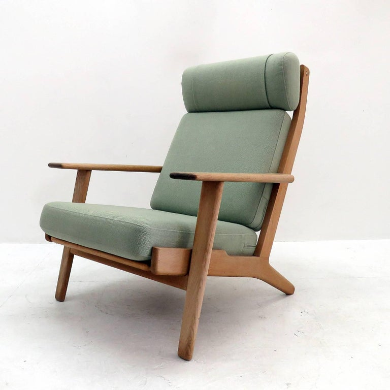 Wonderful high back lounge chair GE290 by Hans J Wegner for GETAMA, solid oak frame with nice patina and original cushions upholstered with light green wool fabric, marked.