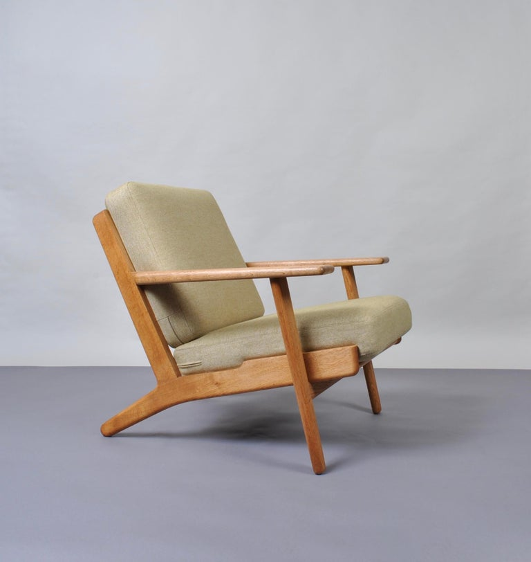 An original 1950s Hans J Wegner GE290 lounge chair in oak with new camira upholstery. Produced by Getama, Denmark. Custom Reupholstery is also available. Original stamp intact