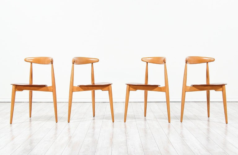 Set of four 'Heart' shaped dining chairs designed by Hans J. Wegner for Fritz Hansen in Denmark in 1952. Like many of Wegner's designs, the model FH-4103 show a functional and thoughtfully mix of materials in construction demonstrating his excellent