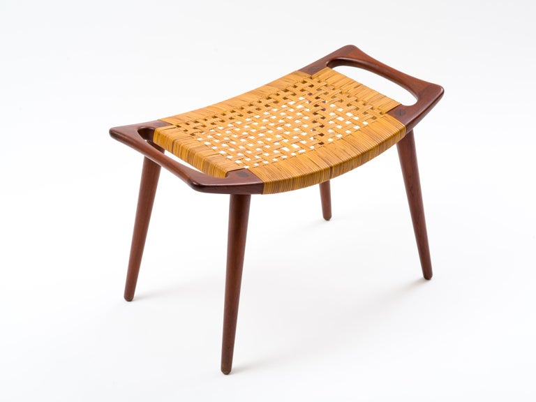 A handled stool, model JH 539, in solid teak with caned seat by Hans Wegner and built by cabinetmaker Johannes Hansen. In lovely, all original condition, this example retains its original caning which exhibits just a few small, inconspicuous breaks.