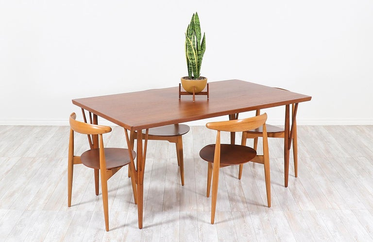Stylish dining table/desk designed by Hans J. Wegner for Johannes Hansen in Denmark, circa 1950s. This Classic model JH-561 table features a solid teak wood rectangular top and angled legs with stretchers adding a Minimalist and clean modern look.