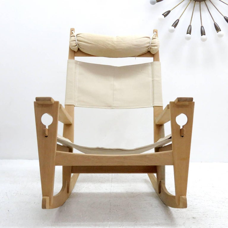 Wonderful rocking chair 'Keyhole' model GE-673, by Hans Wegner for GETAMA, designed in 1967, oak frame with natural linen of later date and original head rest, all wood joints without metal hardware featuring the unique keyhole-shaped joinery that