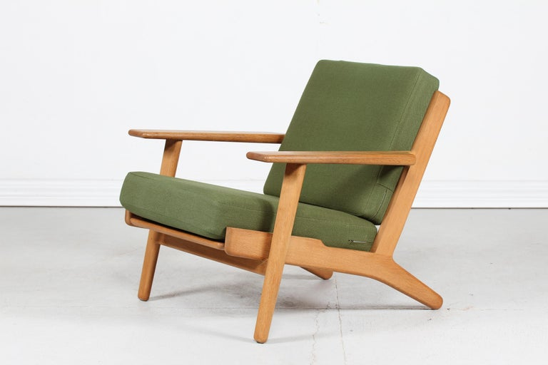 Lounge chair model GE 290 by the danish designer Hans J. Wegner in 1953 This chair is manufactored in the 1970s of genuine oak with good patina and feature cushions with green wool fabric The chair remain in very good condition with great patina