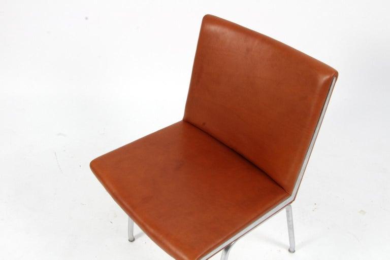 Hans J. Wegner lufthavnsttole designed for Kastrup Airport. New upholstered with Cognac aniline leather.  Base and sides in steel.  Model AP38, made by AP stolen.