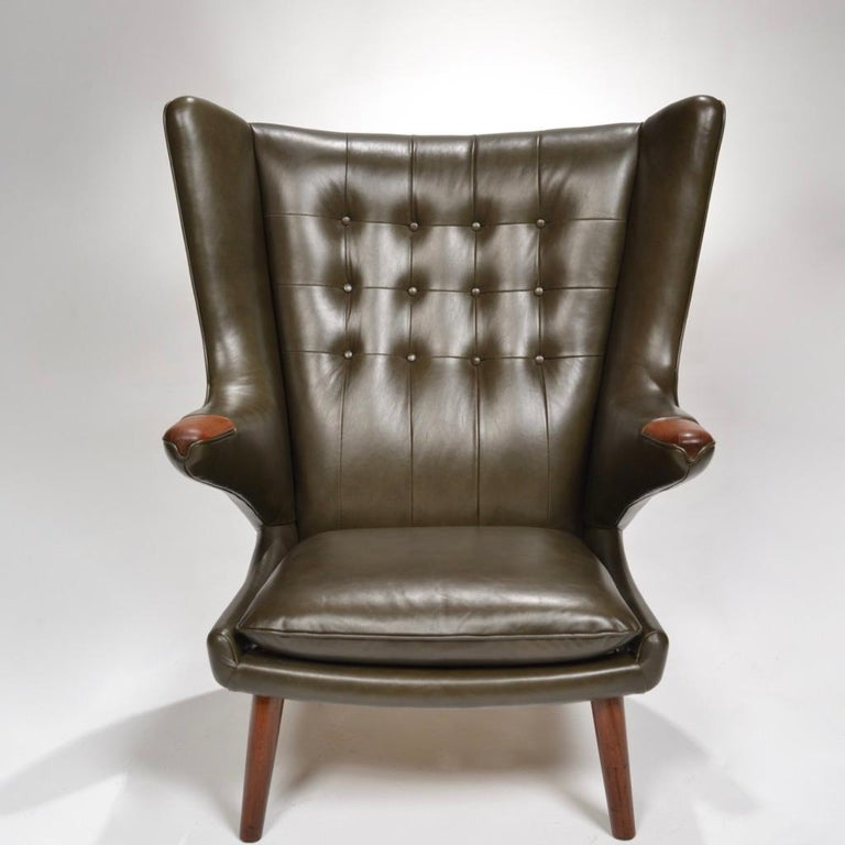 Hans J. Wegner for AP Stolen model AP-19 'Papa Bear' chair, designed in 1951. Considered one of Wegner's most desirable and comfortable chairs. This chair has been professionally reupholstered in a buttery smooth dark green leather. The teak