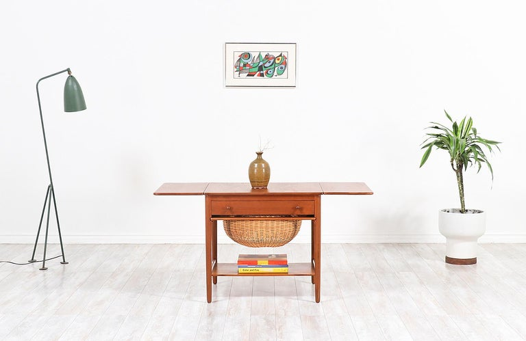 Danish modern sewing table designed by fame architect, Hans J. Wegner. This example was designed in collaboration with the Danish company Andreas Tuck who made most of the tables he designed in Denmark during the 1950s. Like every Wegner design, the