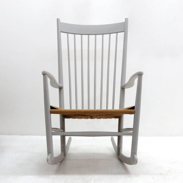 Wonderful model J16 rocking chair by Hans Wegner for FDB Møbler, designed in 1944, in light-gray painted beech with woven paper cord seat. This example was produced in 1961, features a tall spindle back, gracefully curvaceous arms and blade-style