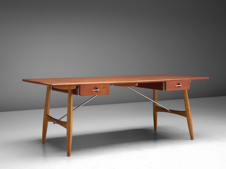 Hans J. Wegner for Johannes Hansen, desk JH571, teak, oak and metal, Denmark, 1953  Wegner designed the JH571 desk in 1953. It features a rectangular tabletop, beneath hanging two drawers with keywhole on each side. Two paired legs on the short side