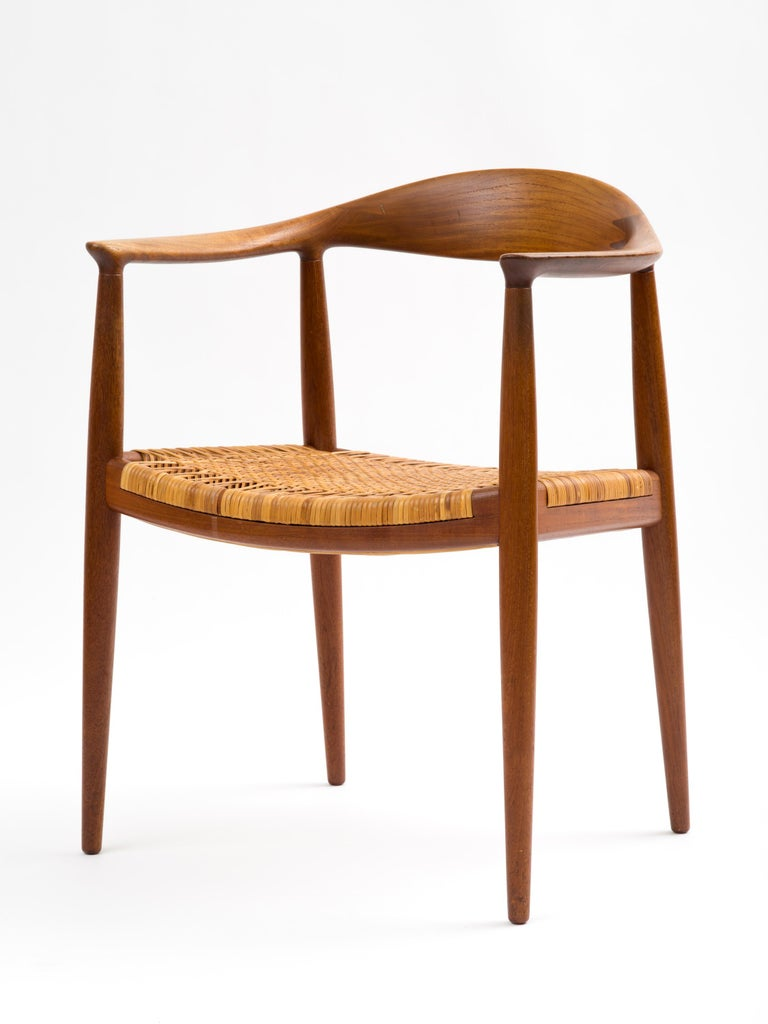 A beautiful example of Hans Wegner's timeless 'The Chair' or 'Round Chair' built by cabinetmaker, Johannes Hansen, in solid teak with its *original* cane seat. The caning is 95% intact and what few breaks there are not ultimately distracting. A fine