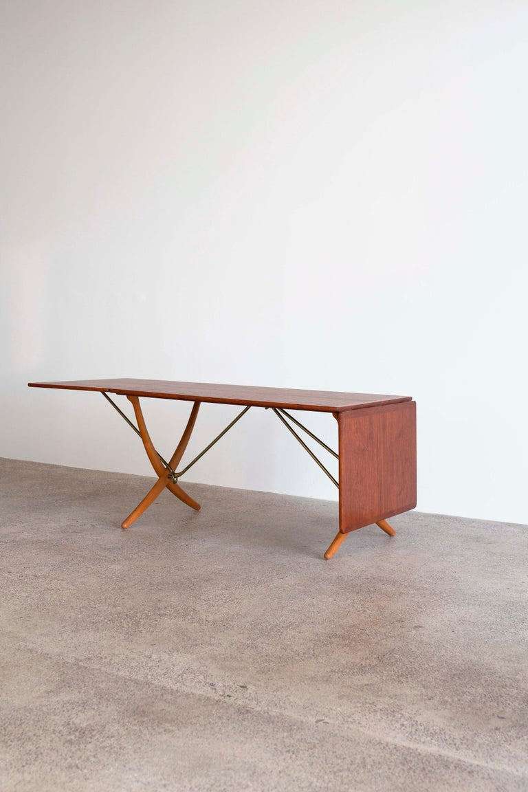 Hans J. Wegner teak dining table with two drop-leaves, cross-legs of patinated beech and stretchers of brass. Very fine condition.   Designed by Wegner 1950 and manufactured by cabinetmaker Andreas Tuck, Denmark, model AT304.   Measuring 128 cm