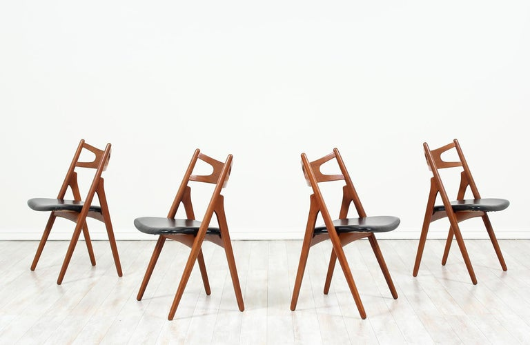 """Set of four iconic """"Sawbuck"""" CH-29 dining chairs designed by Hans J. Wegner for Carl Hansen & Søn in Denmark in 1952. This chair is defined by its A-shaped frame which can be seen from the profile view. This set is sturdily but simply constructed in"""