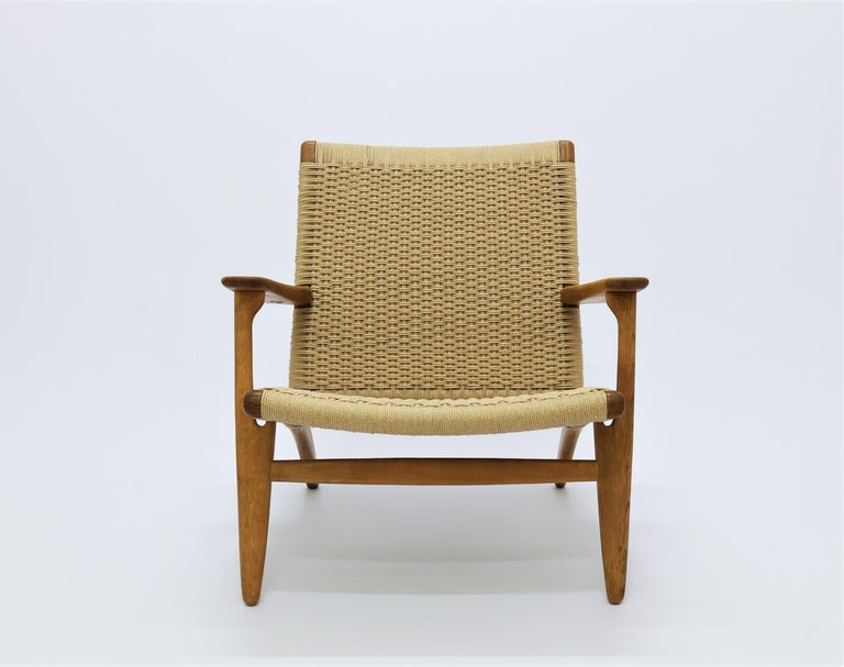 Beautiful vintage lounge chair model CH-25 by Danish Designer Hans J. Wegner for Carl Hansen & Son. This is a model from the very early production of the chair which and it has a perfect patina to the wood. It has been refinished with all new paper