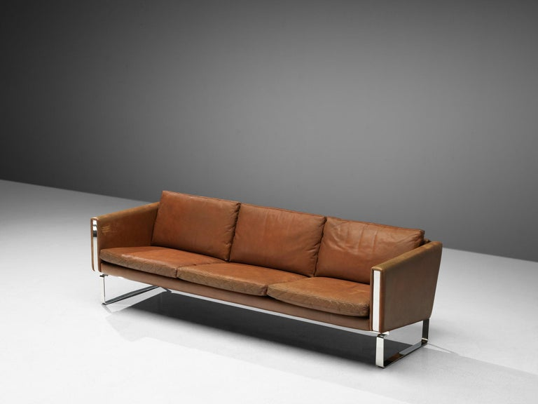 Hans J. Wegner for Carl Hansen & Søn, sofa, leather and chrome, Denmark, 1970s.  The CH103 sofa by Hans J. Wegner for Carl Hansen & Søn is a modern 3-seat sofa ideal for contemporary interiors. This brown leather sofa with a square steel base on