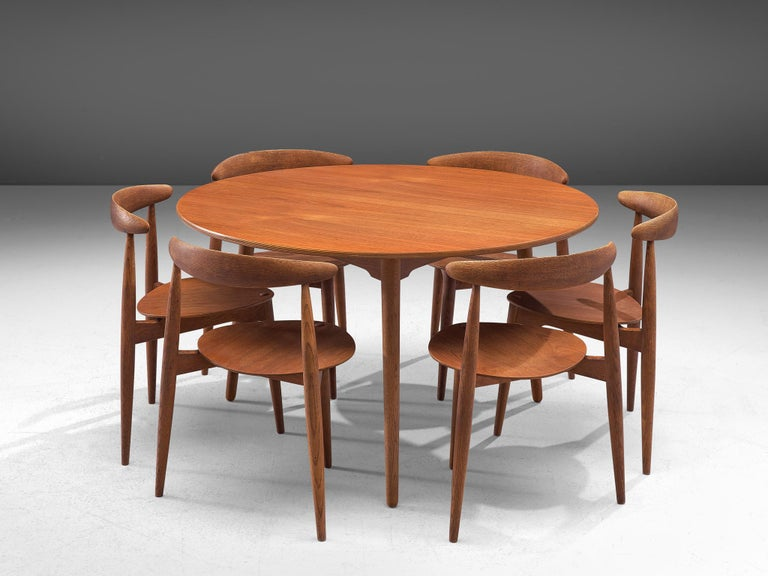 Hans J. Wegner for Fritz Hansen, set of 6 Heart chairs FH4103 and dining table, teak, Denmark, 1953.  This dining set, consisting of a round dining table and six dining chairs, is designed by Hans Wegner in 1952. The chairs are designed to take up
