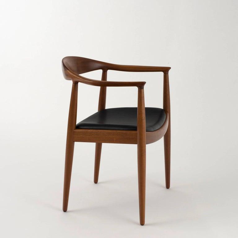 Hans J. Wegner model JH503 in teak. Seat upholstered with black leather. Executed by Johannes Hansen, Copenhagen, Denmark.