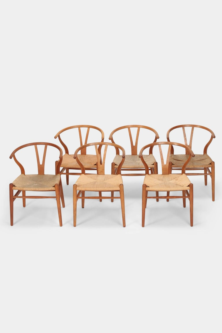 "Hans J. Wegner ""Y-Chairs"" model CH24 manufactured by Carl Hansen & Son in the 1950s in Denmark. Six so called ""Wishbone Chairs"" with a solid oak wood frame and cord seats. Manufacturer stamp on the bottom. The seat of the chairs have different"