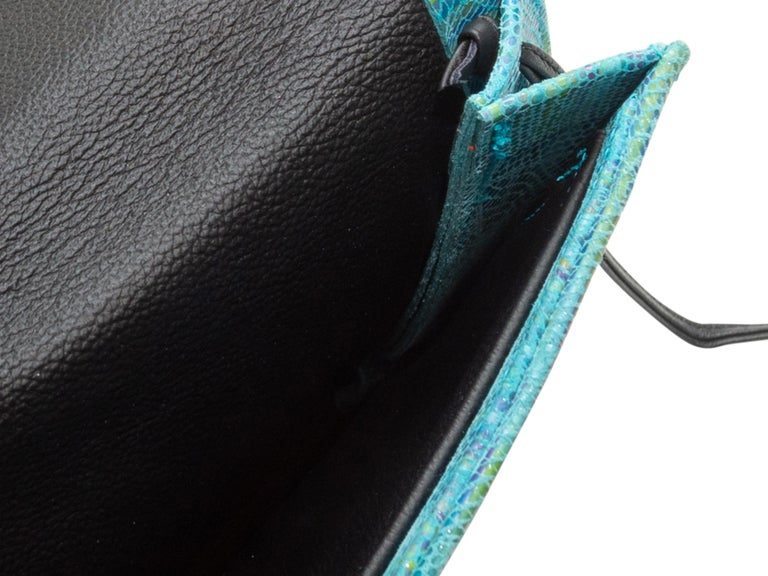 Product details: Turquoise iridescent embossed leather square crossbody bag by Hans Koch. Black leather shoulder strap. Magnetic closure at front flap. 8