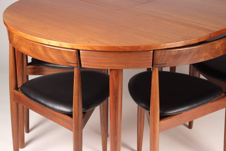 Scandinavian Modern designed, rare teak and leather model Roundette dining table and six chairs. The table expands from a round that accommodates four chairs neatly tucked around its outer rim, up to an expansive roundel which you can then pull up