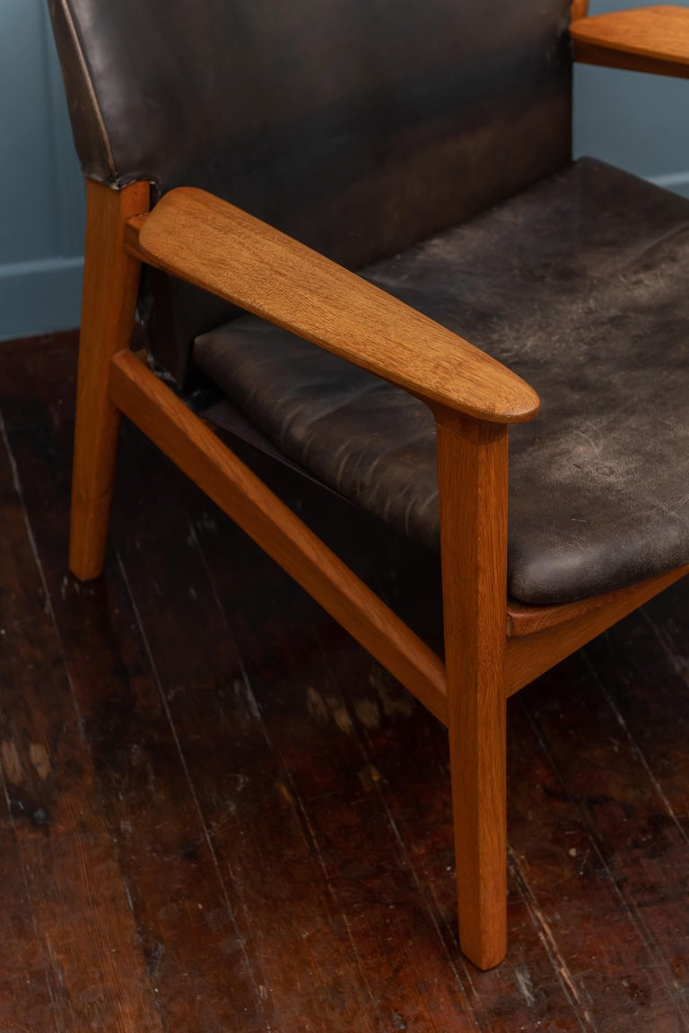 Hans Olsen design sculpted oak and leather lounge chair, 1953, Denmark. Original leather in good patinated condition, frame has a warm inviting oil finish and new seat straps underneath.