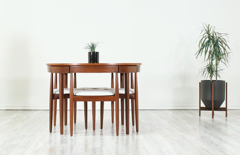 "Unique ""Roundette"" dining set designed by Hans Olsen for Frem Rølje in Denmark, circa 1960s. This striking dining set features a teak wood round table and four dining chairs. The dining chairs seamlessly tuck into the table with their curved back"