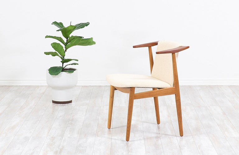 Beautiful modern armchair designed and manufactured by architect and Industrial designer Hans Olsen in Denmark circa 1950s. This iconic chair features an oak and teak wood construction for an exceptional mix of quality materials while providing a