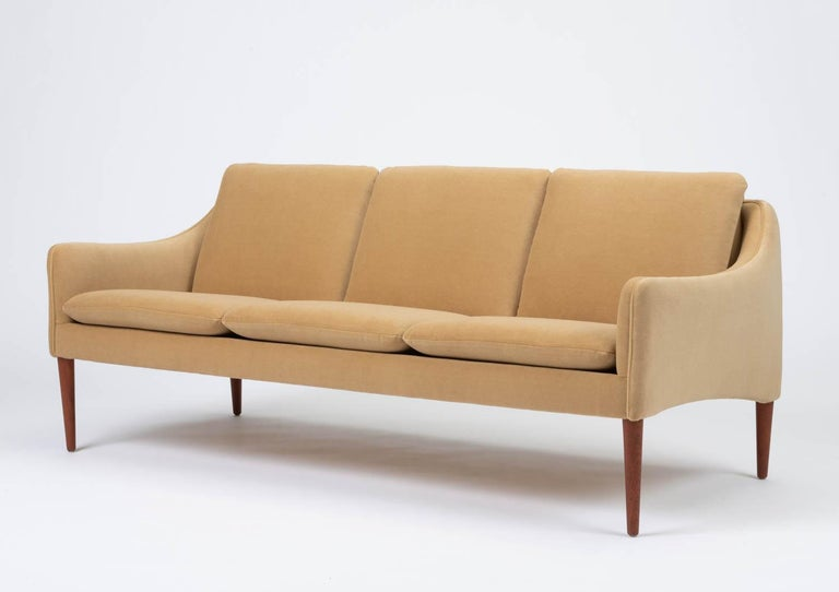Three seat Minimalist sofa by Danish designer Hans Olsen for CS Møbler, circa 1960. The sculpted frame has been newly recovered in a sophisticated camel colored Italian 100% mohair and the straps have been replaced with new webbing. The tapered teak