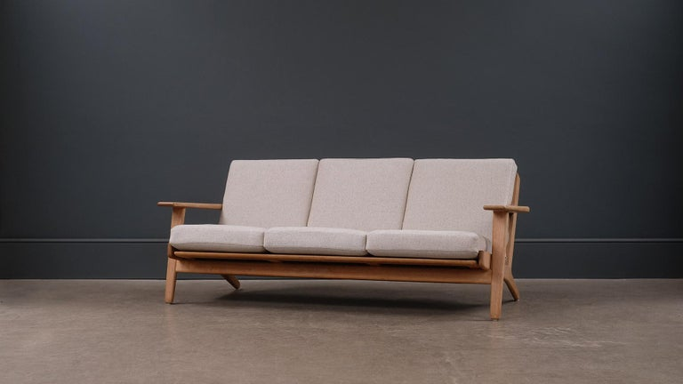 Classic three-seat sofa model GE290 designed by Hans Wegner for GETAMA, Denmark. Solid oak frame with fully reconditioned and reupholstered original sprung cushions.
