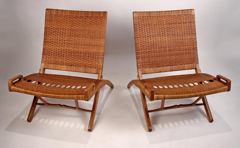 This pair of Danish modern masterpieces is in excellent condition with no breaks to the cane. The oak is also in fine condition. Original 1950s JH stamps are visible on both chairs.