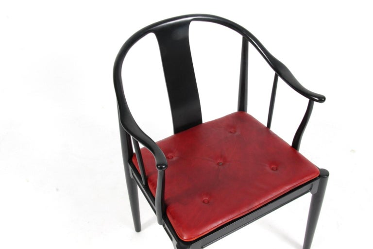"""Hans J. Wegner famous and beautiful chair is an adaptation of an old Chinese chair of the Ming dynasty; """"China Chair"""". A very comfortable armchair made in newly lacquered black wood. Loose seat cushions upholstered with patinated Indian red leather,"""