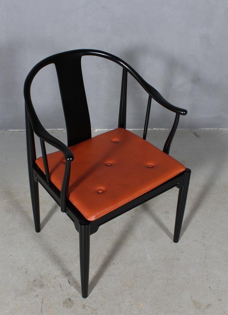 "Hans J. Wegner famous and beautiful chair is an adaptation of an old Chinese chair of the Ming dynasty; ""China Chair"". A very comfortable armchair made in newly lacquered black wood. Loose seat cushions upholstered with patinated tan leather, fitted"