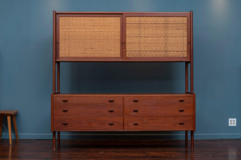 Hans Wegner credenza or hutch for RY-Mobler, Denmark. High quality construction and materials executed by Hans Wegner for Ry Mobler, Model RY 20. Beautiful warm colored teak with dramatic grains thorought and two caned sliding doors with two