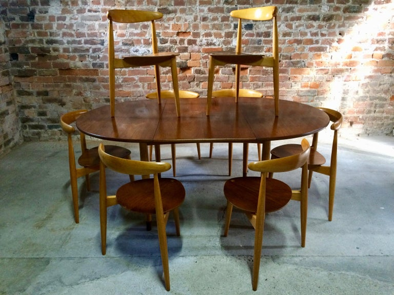 Hans J Wegner 'The Heart' dining suite made in Denmark by Fritz Hansen circa 1950, with eight 'heart' chairs Model FH4103 made from teak and beech frames, the chairs are all stackable, the matching table is an extremely rare four legged version with