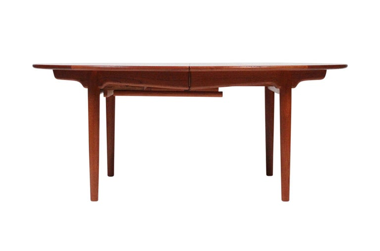 Very rare and large dining table with a solid teak top and oak legs, model JH-567 designed by Hans Wegner. Produced by cabinetmaker Johannes Hansen in Denmark. Three interlocking leaves are removable, when fully extended seats 12-14 people. This