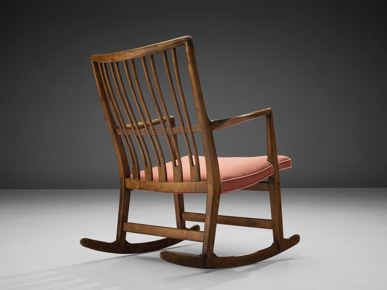 Hans Wegner for Mikael Laursen, ML-33 rocking chair, beech, fabric upholstery, Denmark, 1940s   Hans Wegner designed the 'ML-33' rocking chair for Laursen in the 1940s. The wooden frame features an elegant backrest with slim, vertical slats