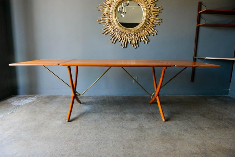Early Hans Wegner for Andreas Tuck Model AT-304 drop leaf dining table, circa 1955. Original excellent condition, hardly used with extremely light wear on feet and top, almost perfect with no need for restoration. Solid brass stretcher bars and