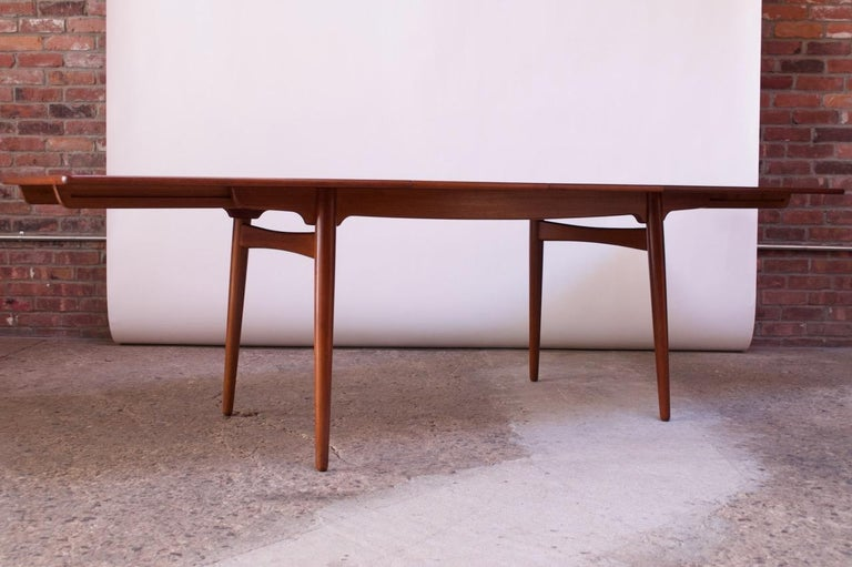 Model AT-310 teak dining table by Hans J. Wegner for Andreas Tuck, (Denmark, circa 1960). Composed of a teak surface supported by tapered, teak legs. Includes two additional 15.75