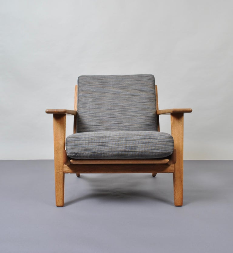 An original 1950s Hans J Wegner GE290 lounge chair. Produced by GETAMA, Denmark. European oak frame with all new upholstery. Custom re-upholstery is available. Original stamp intact