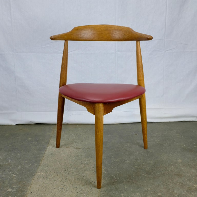 Three-legged dining chair designed by Hans Wegner in 1953 and made in Denmark by Fritz Hansen. Known as the 'heart chair' for the shape of its seat.  Frame constructed in oak with red leatherette seat. Stamped with 'FH' and 'Denmark' across the