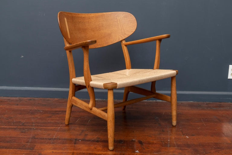 Hans Wegner design teak and oak lounge chair, model CH-22 for Carl Hanson & Son, Denmark. Excellent structural condition with original finish and a new woven seat.