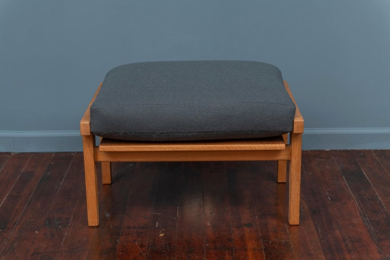 Hans Wegner design ottoman for GETAMA, Denmark. Model GE 290 solid oak frame in very good original condition with a newly upholstered wool cushion, signed.