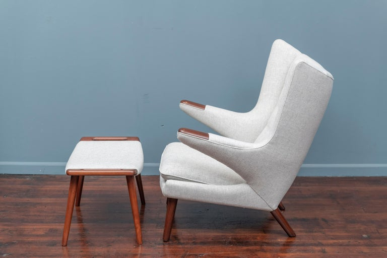 Hans Wegner papa bear chair and ottoman, the more desirable early teak legs and arm pads version. Newly refinished and upholstered in a very light grey Danish wool, ready to enjoy.
