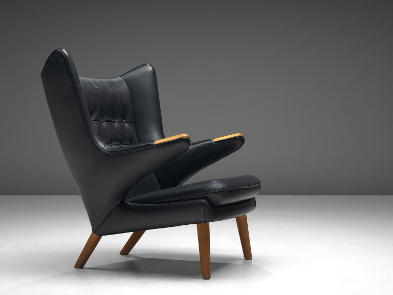 Hans J. Wegner by AP Stolen, lounge chair Model AP 19 'Papa Bear', black leather and beech, Denmark, 1951 design, production late 1950s.  This semi-wingback armchair, has an open expression in contrast with its historical ancestors. Wegner made a